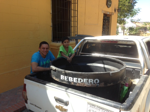 Filling up a tank of water for families in Mompos from the well at the Casa Amarilla