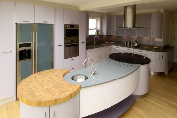Curved island counter with integrated preparation area, sink and hob