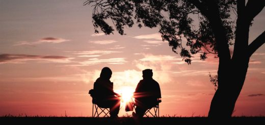 Photo of a couple sitting in front of a sunset during retirement