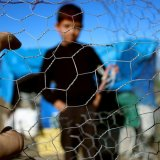 Image of a migrant child behind a fence