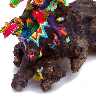 Colorful artwork called Pruned by a Druid from the series Origin of Joy, A piece of wood with both painted as 3-D objects made from fabric bursting out.