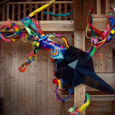 This is an Origin of Joy installation showing a large geometric shaped sculpture with colorful tentacles reaching out to take over the surroundings.