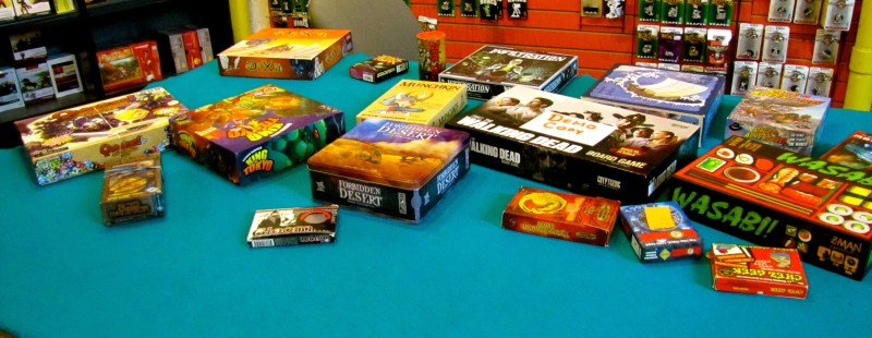 A table of boardgames for people to pick up and play.
