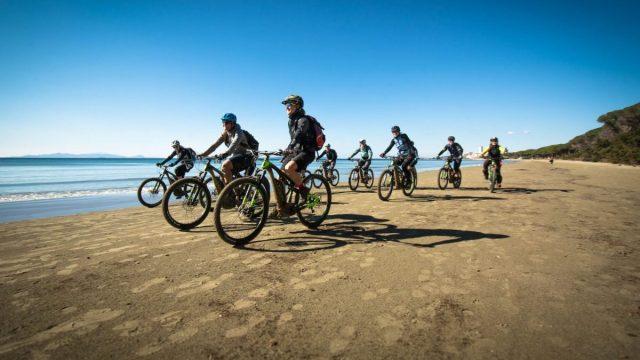 Cycling in winter women on the beach in Follonica