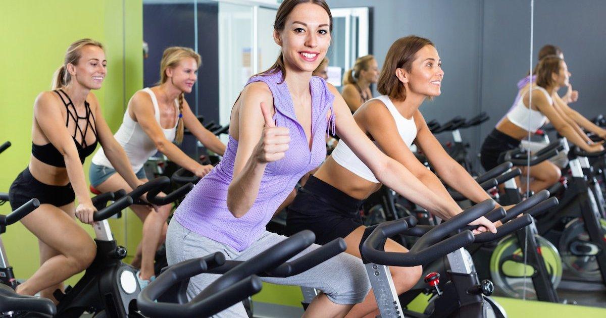 ragazze che si allena in palestra su una cyclette