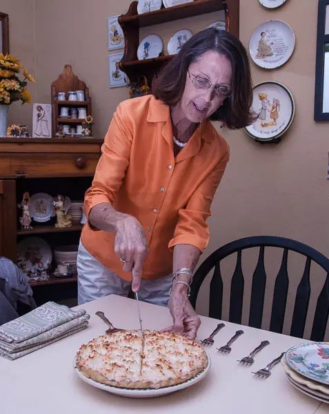 Patty Youngpeter slicing a piece of her coconut creme cake.