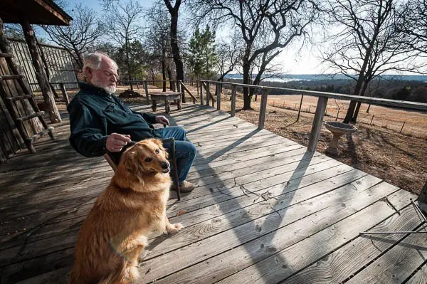 Tommy Smith with his dog on the back porch of his Stillwater home.