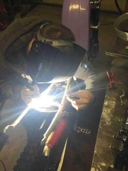 Tombo Racing's Jimmy Cook welding the aluminum frame on my Aprilia 280 Climber observed trials motorcycle.
