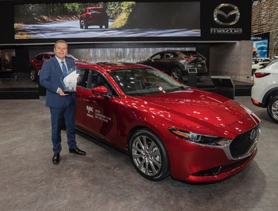 David Klan, President  CEO, Mazda Canada holding a prize for a 2020 AJAC Canadian Car of a Year in front of a award-winning Mazda3 (CNW Group/Mazda Canada Inc.)
