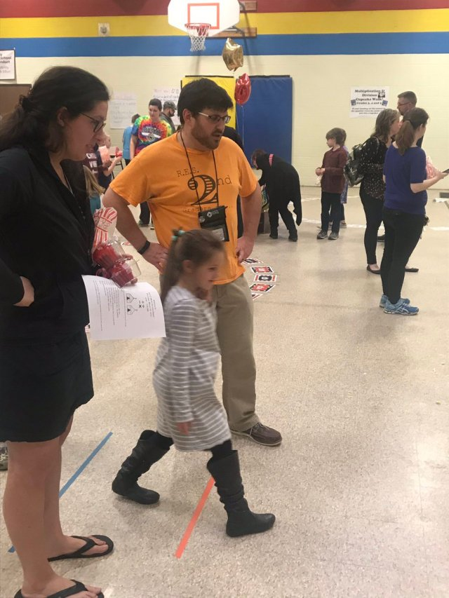 Child with teachers at Math Carnival