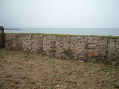 A Gabion retaining wall a grass face on top.