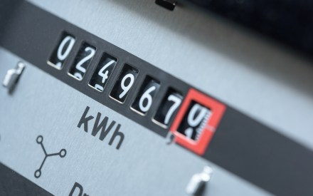 grey electricity meter displaying the current energy use in kWh