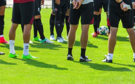 football team training players stood in circle legs only