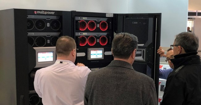four male data centre professionals looking at Riello UPS Multi Power (MPW) uninterruptible power supply with illuminated red fans at DCW 2019