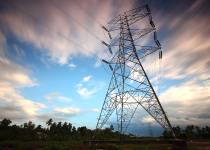 upward shot of power transmission lines with cloudy background