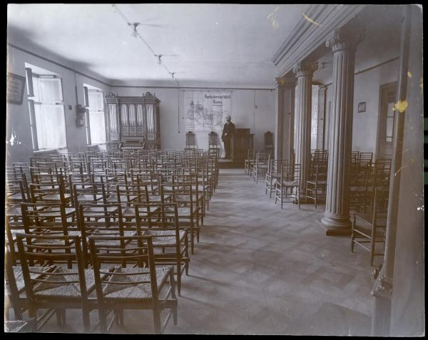 "1913-1915 - Riga, Latvia - Julius T. Boettcher standing in interior of the Adventist meeting hallReverse reads: ""Interior of the S.D.A. meeting-hall Riga, Russia"", so could be prior to 1918. Map and wall hangings are in German."