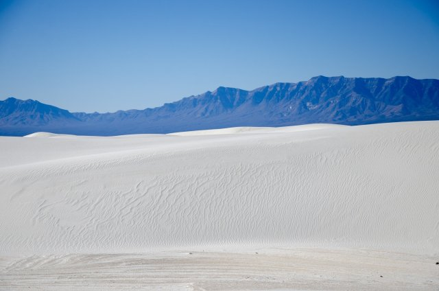 Mountains are shown behind the sea of dunes