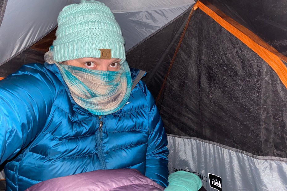 A woman bundled in a tent is shown while Cold Weather Camping
