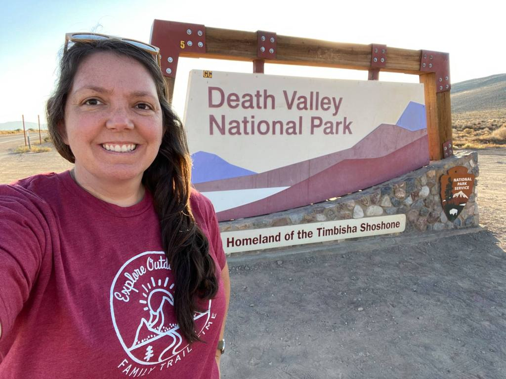 The authors stands by the Death Valley sign in the summer