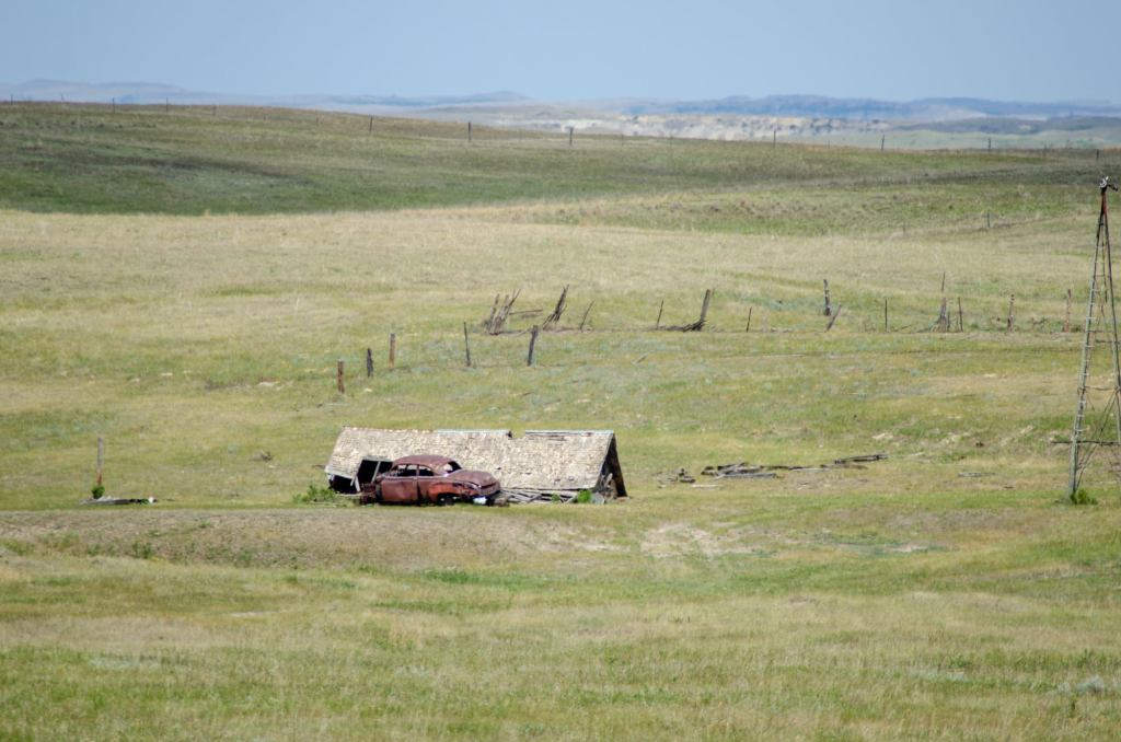 A old house and car are shown on the road to the Elkhorn Ranch Unit