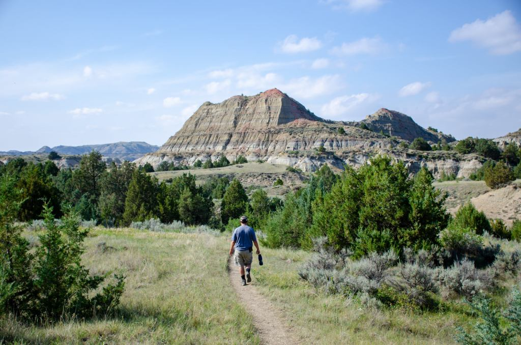 A man walks along the trail with a butte in the background