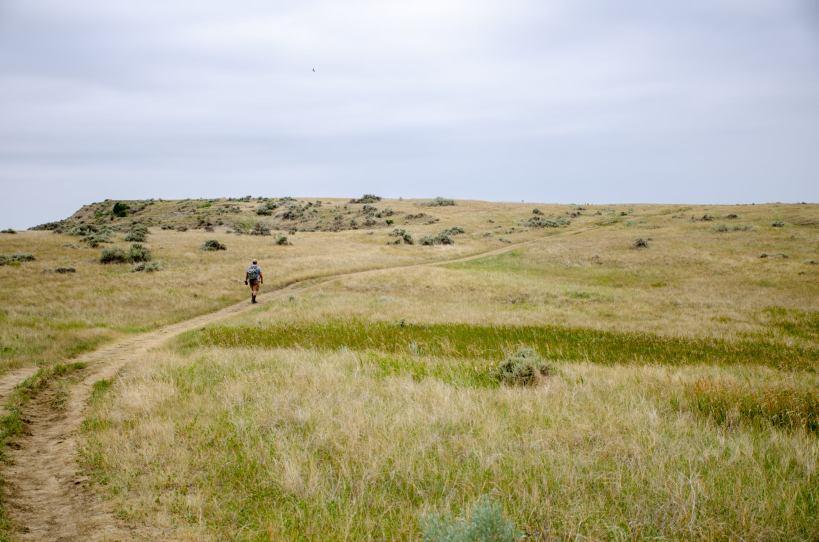 A hiker walks across the prairie