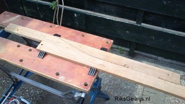 De houtkeuze is oud afval hout, deze planken zijn van gesloopte oude hardhouten pallets. Mooi hout om een standaard van te maken. Omdat ik een kromme boog heb bedacht lijm ik eerst twee delen tegen elkaar aan. Deze zijn ook onderling met deuvels verbonden. Zo ontstaat er een blinde verbinding. Door het vast persen tussen een werkbank is de naad ook zo goed als onzichtbaar. Wanneer dit droog is kan de vorm getekend worden.
