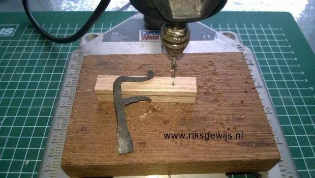 Het boren van de gaatjes kan gemakkelijkst met een kolomboormachine. Toch gaat het ook wel uit de hand, ik heb het geluk een kolomboor te hebben met een Dremel zodat de gaatjes mooi haaks zullen staan. Een klosje hout voor het boren onder het werkstuk is handig om splinters te voorkomen. Omdat ik 4MM draadeind gebruik boor ik gaatjes van 3,2MM voor. Daardoor kan straks het draadeind er strak in gedraaid en gelijmd worden.