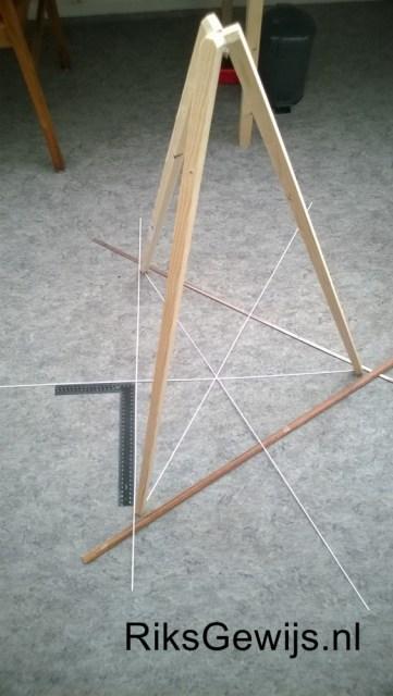 Het uitzetten van de driepoot. Door een gelijkbenige driehoek uit te zetten en daar het midden punt in uit te zetten kan er door een schietlood het midden gevonden worden waar de drie poten aan elkaar gelijmd en geschroefd worden. Hiervoor is wel een klosje hout wat in de juiste driehoek vorm is gezaagd.