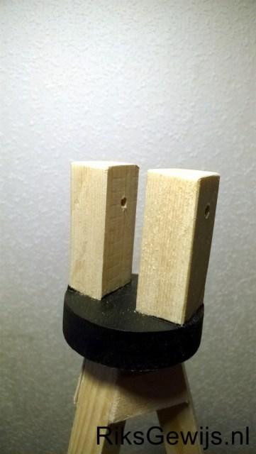 De afwerking van de bovenkant van de driepoot. Een ronde schijf waarop twee blokjes geschroefd en gelijmd zijn. Hiertussen dan de hals van de lamp geklemd worden met een bout en vleugelmoer. Dan is de lamp ook in hoogte verstelbaar.