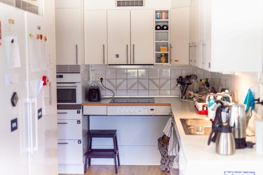 Ett kök med köksbänkar och skåp med luckor. Ett kylskåp med frys synes på vänster sida.