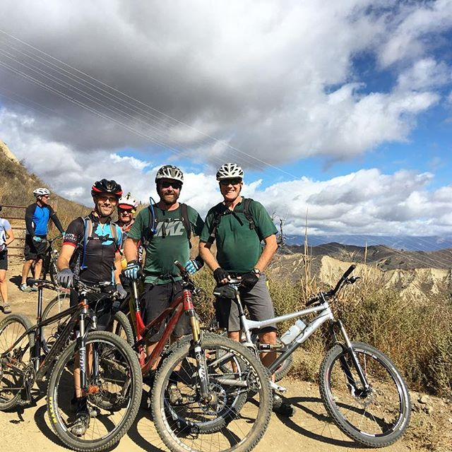 Three men standing in front of bikes in the mountains.