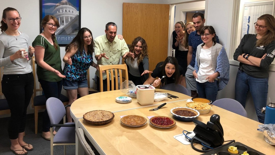 Group of people excited about pies on the table.