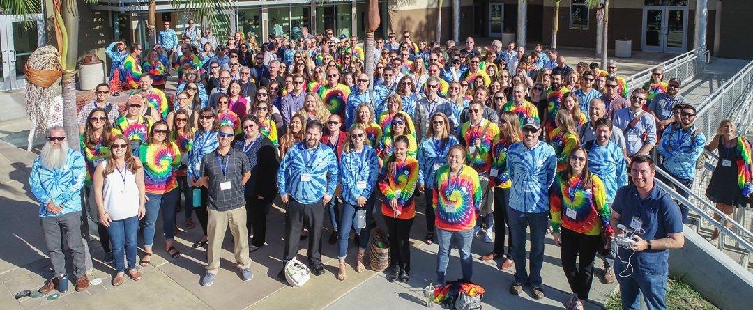 Group of people wearing tie dye t-shirts smiling.