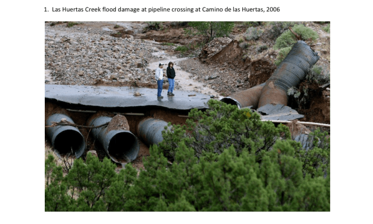 "Figure 1: Example of flood damage in Placitas, NM that ruptured ""underground"" pipelines buried in a streambed"