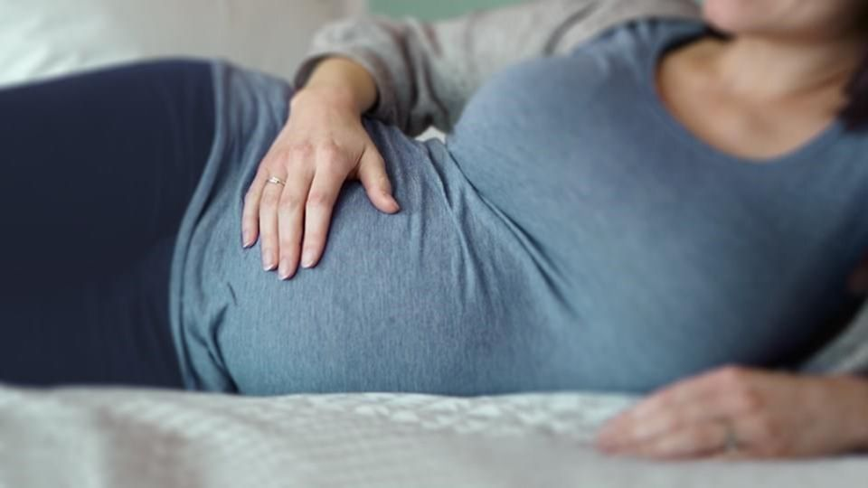 a picture of a pregnant woman laying down