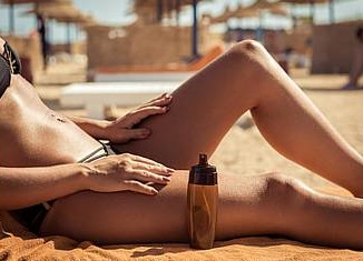 a woman applying tanning oil