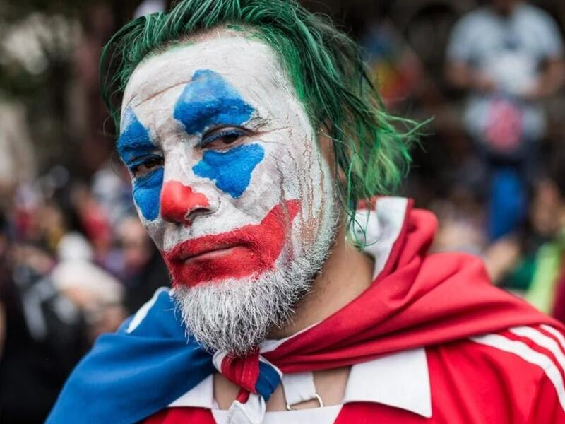 Protester with the painted face of Joaquin Phoenix's Joker. A look at the modern protester and the Joker mask is at Riot Material