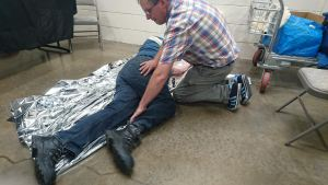 man putting another man in the recovery position with foil blanket underneath