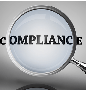 An image of a magnifying glass looking at the word Compliance