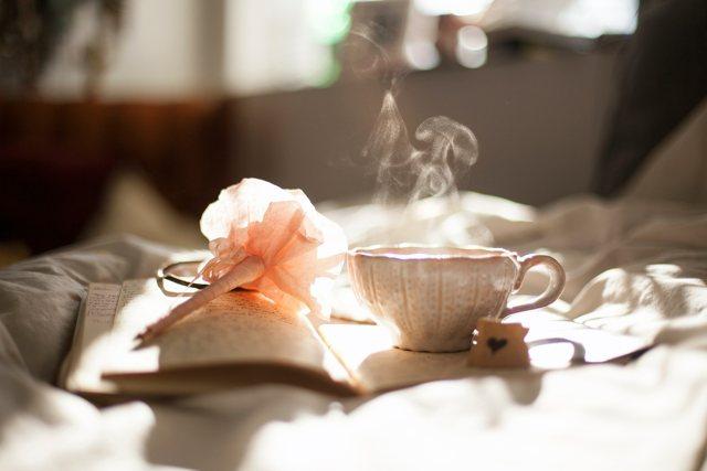 Lavorare da casa: un quaderno e una tazza di caffè... sul letto
