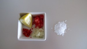 Kleingeschnittene Chilli, Peperoncini und Zwiebeln mit einem Schnitz Zitrone und Meersalz