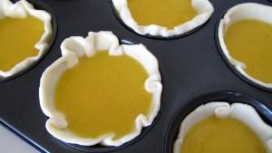Blätterteig in Muffinblech werden mit der Puddingmasse befüllt
