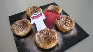 Fertige Pasteis de Nata mit Trikot-Fähnchen der beiden Mannschaften von Deutschland und Portugal