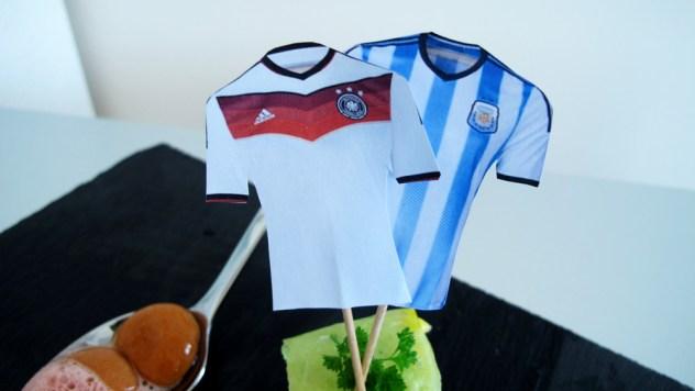 Trikot-Fähnchen der beiden Mannschaften auf argentinischer Currywurst