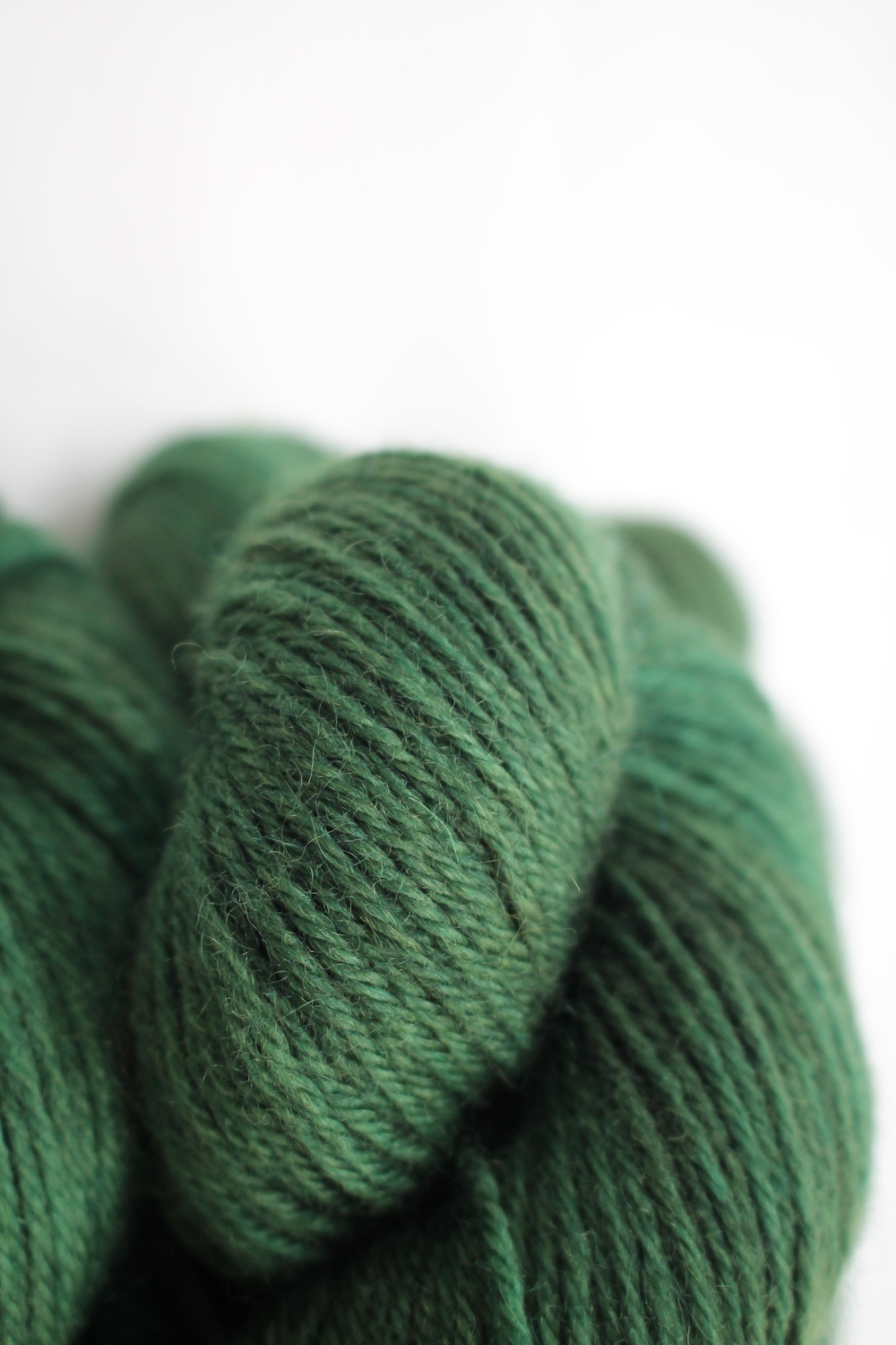 A pile of skeins of Nene DK in forest green