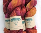 Skeins of Nectarine dyed in variegated warm purples, browns, and golden mustard
