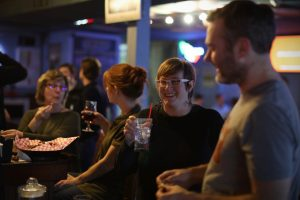 Friends having a laugh over drinks at Helen's North Kansas City dive bar