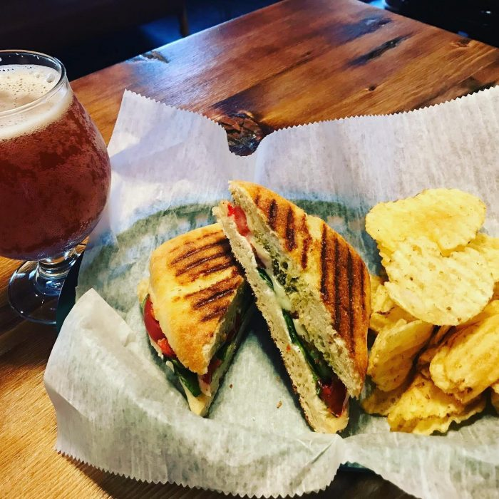 Freshly made panini, halved and served with chips and a Brewkery kombucha
