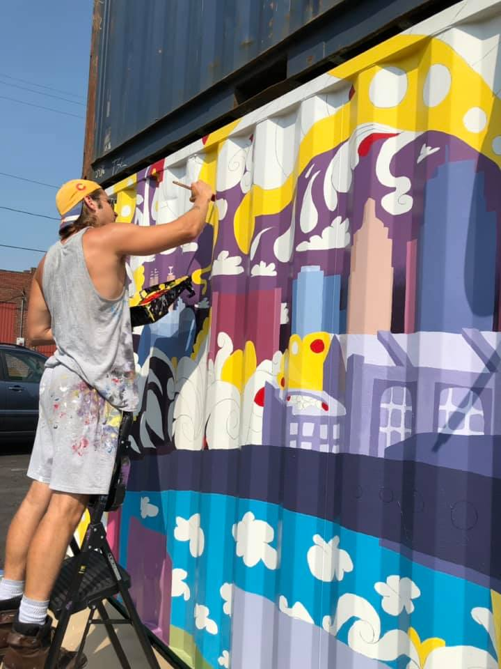 Artist works on a mural painted on the side of Iron District shipping containers